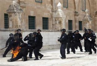 An Israeli police officer falls, engulfed in flames after Palestinian protesters threw firebombs during clashes in Jerusalem's Old City