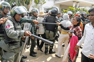 Garment workers confront police officers during a protest in front of a factory in Kampong Speu province