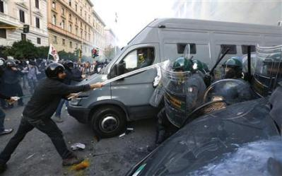A protester clashes with Guardia di Finanza as they respond to a protest in front of the Ministry of Finance building in downtown Rome