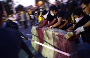 Anti-government protesters tear down barricades during a demonstration outside Government House in Bangkok