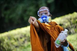 A Buddhist monk wearing a gas mask points towards police positions as they clash with anti-government protesters near the Government House in Bangkok