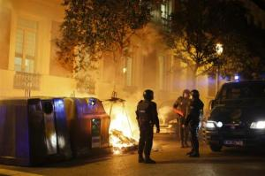 Riot police stand next to a fire set by demonstrators in Madrid, during a demonstration in support of protesters in Burgos opposing an urban project