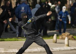 A protester throw stones at police during a demonstration demanding the resignation of the government in Podgorica