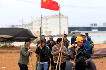 Villagers guard the entrance to Fuyou village next to the Chinese national flag in Jinning county, Kunming