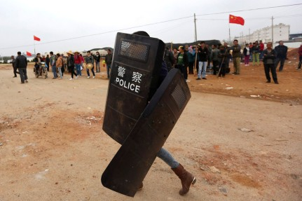 A villager carries police shields taken from police injured during clashes between villagers and construction site workers at Fuyou village in Jinning county, Kunming