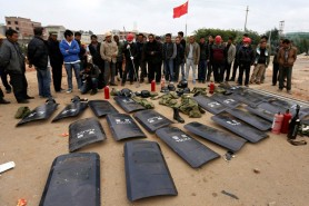 Villagers stand behind shields taken from police injured during clashes at Fuyou village in Jinning county, Kunming