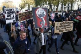 Demonstrators pass Downing Street as they participate in a protest against student loans and in favour of free education, in central London